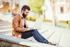 Giovane uomo bello barbuto che si siede sulle scale facendo uso del computer portatile in città Immagine Stock