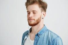 Giovane uomo bello che ascolta il flusso continuo della musica in cuffie con gli occhi chiusi che godono sopra il fondo bianco fotografia stock libera da diritti