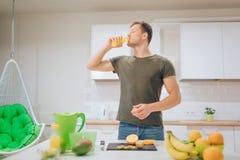 Giovane uomo bello che beve succo d'arancia fresco nella cucina Alimento sano Pasto vegetariano Disintossicazione di dieta immagini stock