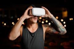 Giovane uomo bello che indossa una cuffia avricolare di realtà virtuale Immagini Stock Libere da Diritti
