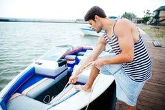 Giovane uomo bello che prepara barca per iniziare un viaggio Fotografia Stock