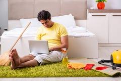 Giovane uomo bello che pulisce la camera da letto e che si siede al compu immagine stock libera da diritti