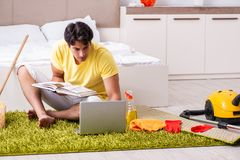 Giovane uomo bello che pulisce la camera da letto e che si siede al compu immagini stock libere da diritti
