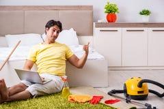 Giovane uomo bello che pulisce la camera da letto e che si siede al compu fotografia stock
