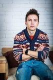 Giovane uomo bello che si siede su una sedia Fotografia Stock