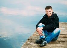 Giovane uomo bello che si siede sul pilastro di legno Fotografia Stock Libera da Diritti