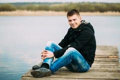 Giovane uomo bello che si siede sul pilastro di legno Immagini Stock