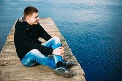 Giovane uomo bello che si siede sul pilastro di legno, rilassarsi, pensante, Fotografie Stock