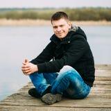 Giovane uomo bello che si siede sul pilastro di legno, rilassarsi, pensante, Immagine Stock