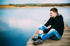Giovane uomo bello che si siede sul pilastro di legno, rilassarsi, pensante, Fotografie Stock Libere da Diritti