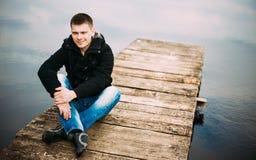 Giovane uomo bello che si siede sul pilastro di legno, rilassarsi, pensante Fotografia Stock