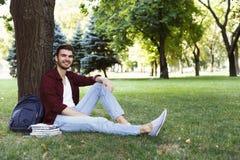 Giovane uomo bello che si siede sull'erba all'aperto Immagine Stock Libera da Diritti