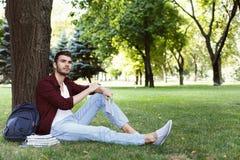 Giovane uomo bello che si siede sull'erba all'aperto Fotografia Stock Libera da Diritti