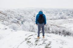 Giovane uomo bello che sta sulla collina in un giorno di inverno Immagine Stock