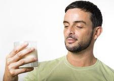 Giovane uomo bello con il latte alimentare della barba Immagine Stock