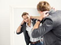 Giovane uomo bello con indifferenza vestito davanti allo specchio immagine stock libera da diritti