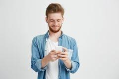Giovane uomo bello in cuffie che sorride esaminando telefono che ascolta il flusso continuo della musica sopra fondo bianco immagine stock libera da diritti