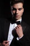 Giovane uomo bello di affari che ripara la sua cravatta a farfalla fotografie stock