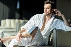Giovane, uomo bello di mattina che pensa mentre sedendosi in una r immagine stock