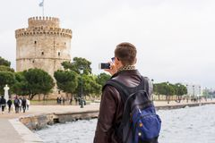 Giovane uomo bello in occhiali da sole, turista, con lo zaino che prende ad immagini su uno smartphone una torre bianca nel centr fotografia stock libera da diritti
