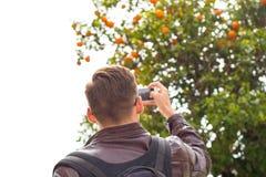 Giovane uomo bello in occhiali da sole, turista, con lo zaino che prende le immagini su un arancio dello smartphone immagini stock libere da diritti