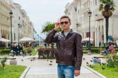 Giovane uomo bello in occhiali da sole, turista, sulla via di Aristotele del pedone nel centro di Salonicco, la Grecia immagine stock