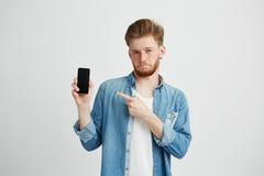Giovane uomo bello sicuro che esamina macchina fotografica che indica dito al telefono in sua mano sopra fondo bianco Immagine Stock Libera da Diritti