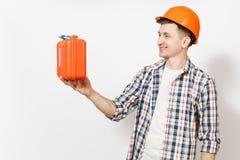 Giovane uomo bello sorridente in cassa arancio protettiva della tenuta dell'elmetto protettivo con gli strumenti o la cassetta po immagine stock