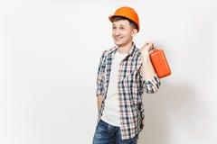 Giovane uomo bello sorridente in cassa arancio protettiva della tenuta dell'elmetto protettivo con gli strumenti o la cassetta po immagini stock libere da diritti