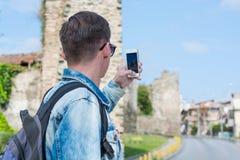 Giovane uomo bello, turista, con lo zaino che prende ad immagini su uno smartphone la torre di Trigonion a Salonicco, la Grecia fotografie stock libere da diritti