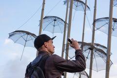 Giovane uomo bello, turista, con lo zaino prendendo le immagini su uno smartphone immagini stock