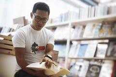 Giovane uomo castana dagli occhiali che si siede accanto agli scaffali di libro e che apre un libro immagini stock libere da diritti
