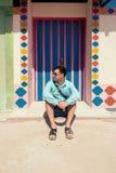 Giovane uomo castana, durante in camicia blu, sandali, occhiali da sole, con la borsa Immagine Stock Libera da Diritti
