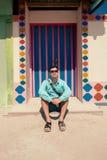 Giovane uomo castana, durante in camicia blu, sandali, occhiali da sole, con la borsa Fotografia Stock