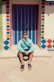 Giovane uomo castana, durante in camicia blu, sandali, occhiali da sole, con la borsa Immagini Stock