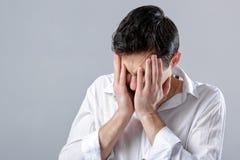 Giovane uomo castana frustrato in camicia con l'emicrania su gray Fotografia Stock
