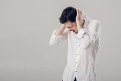 Giovane uomo castana frustrato in camicia con l'emicrania sul BAC grigio Fotografia Stock Libera da Diritti