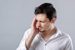Giovane uomo castana frustrato in camicia con l'emicrania sul BAC grigio Immagine Stock