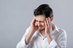 Giovane uomo castana frustrato in camicia con l'emicrania sul BAC grigio Immagine Stock Libera da Diritti