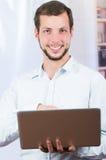 Giovane uomo casuale che per mezzo del computer portatile Immagini Stock Libere da Diritti