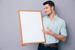 Giovane uomo casuale che presenta qualcosa sul bordo in bianco Fotografia Stock