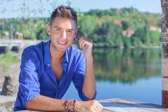 Uomo alla tavola vicino al lago Fotografia Stock