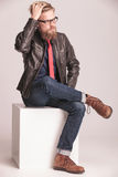 Giovane uomo casuale che si siede su un cubo bianco Fotografia Stock