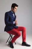 Giovane uomo casuale che si siede su un panchetto Fotografie Stock