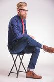 Giovane uomo casuale che si siede su un panchetto Fotografie Stock Libere da Diritti