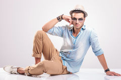 Giovane uomo casuale che si siede sul pavimento Fotografia Stock
