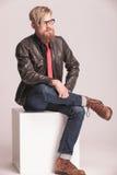 Giovane uomo casuale di modo che si siede su un cubo bianco Fotografia Stock Libera da Diritti