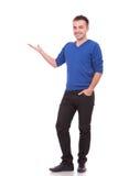 Giovane uomo casuale felice che presenta qualcosa Fotografia Stock Libera da Diritti