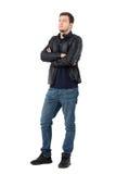 Giovane uomo casuale serio in bomber e jeans con distogliere lo sguardo attraversato di armi Immagine Stock Libera da Diritti