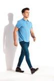 Giovane uomo casuale sicuro nella camminata della camicia e dei jeans di polo Immagini Stock